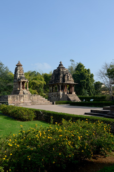 """Khajuraho Temple Complex. Khajuraho - Land Of The Moon God is located in the Indian state of Madhya Pradesh (MP) and roughly 620 kilometers (385 miles) southeast of New Delhi. Khajuraho was the cultural capital of the Chandela Rajputs, a Hindu dynasty that ruled from the 10th to 12th centuries. The temples of Khajuraho are famous for their so-called """"erotic sculptures"""".<br /> <br /> Symbolising a medieval legacy, the Khajuraho temples are a perfect fusion of architectural and sculptural excellence, representing one of the finest examples of Indian art. To some, they are the most graphic, erotic and sensuous sculptures the world has ever known. But Khajuraho has not received the attention it deserves for its significant contribution to the religious art of India - there are literally hundreds of exquisite images on the interior and exterior walls of the shrines.<br /> <br /> Architecturally they are unique. While each temple has a distinct plan and design, several features are common to all. They are all built on high platforms, several metres off the ground. The stone used throughout is either granite or a combination of light sandstone and granite. Each of these temples has an entrance hall or mandapa, and a sanctum sanctorum or garbha griha. The roofs of these various sections have a distinct form. The porch and hall have pyramidal roofs made of several horizontal layers. The inner sanctum's roof is a conical tower - a colossal pile of stone (often 30m high) made of an arrangement of miniature towers called shikharas."""