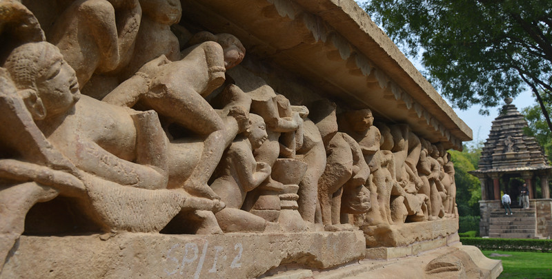 """A few stone carvings depict erotic and sexual acts at Khajuraho. Khajuraho - Land Of The Moon God is located in the Indian state of Madhya Pradesh (MP) and roughly 620 kilometers (385 miles) southeast of New Delhi. Khajuraho was the cultural capital of the Chandela Rajputs, a Hindu dynasty that ruled from the 10th to 12th centuries. The temples of Khajuraho are famous for their so-called """"erotic sculptures"""".<br /> <br /> Symbolising a medieval legacy, the Khajuraho temples are a perfect fusion of architectural and sculptural excellence, representing one of the finest examples of Indian art. To some, they are the most graphic, erotic and sensuous sculptures the world has ever known. But Khajuraho has not received the attention it deserves for its significant contribution to the religious art of India - there are literally hundreds of exquisite images on the interior and exterior walls of the shrines.<br /> <br /> Architecturally they are unique. While each temple has a distinct plan and design, several features are common to all. They are all built on high platforms, several metres off the ground. The stone used throughout is either granite or a combination of light sandstone and granite. Each of these temples has an entrance hall or mandapa, and a sanctum sanctorum or garbha griha. The roofs of these various sections have a distinct form. The porch and hall have pyramidal roofs made of several horizontal layers. The inner sanctum's roof is a conical tower - a colossal pile of stone (often 30m high) made of an arrangement of miniature towers called shikharas."""
