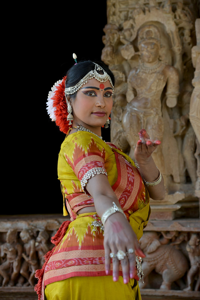 """Odissi dancer Bithika Mistry strikes a dance pose at the Khajuraho Temple.<br /> <br /> <br /> Khajuraho - Land Of The Moon God is located in the Indian state of Madhya Pradesh (MP) and roughly 620 kilometers (385 miles) southeast of New Delhi. Khajuraho was the cultural capital of the Chandela Rajputs, a Hindu dynasty that ruled from the 10th to 12th centuries. The temples of Khajuraho are famous for their so-called """"erotic sculptures"""".<br /> <br /> Symbolising a medieval legacy, the Khajuraho temples are a perfect fusion of architectural and sculptural excellence, representing one of the finest examples of Indian art. To some, they are the most graphic, erotic and sensuous sculptures the world has ever known. But Khajuraho has not received the attention it deserves for its significant contribution to the religious art of India - there are literally hundreds of exquisite images on the interior and exterior walls of the shrines.<br /> <br /> Architecturally they are unique. While each temple has a distinct plan and design, several features are common to all. They are all built on high platforms, several metres off the ground. The stone used throughout is either granite or a combination of light sandstone and granite. Each of these temples has an entrance hall or mandapa, and a sanctum sanctorum or garbha griha. The roofs of these various sections have a distinct form. The porch and hall have pyramidal roofs made of several horizontal layers. The inner sanctum's roof is a conical tower - a colossal pile of stone (often 30m high) made of an arrangement of miniature towers called shikharas."""