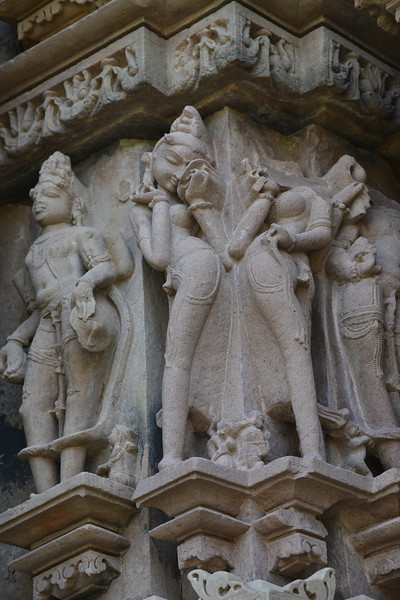 """Detailed carvings on the temple walls. Khajuraho - Land Of The Moon God is located in the Indian state of Madhya Pradesh (MP) and roughly 620 kilometers (385 miles) southeast of New Delhi. Khajuraho was the cultural capital of the Chandela Rajputs, a Hindu dynasty that ruled from the 10th to 12th centuries. The temples of Khajuraho are famous for their so-called """"erotic sculptures"""".<br /> <br /> Symbolising a medieval legacy, the Khajuraho temples are a perfect fusion of architectural and sculptural excellence, representing one of the finest examples of Indian art. To some, they are the most graphic, erotic and sensuous sculptures the world has ever known. But Khajuraho has not received the attention it deserves for its significant contribution to the religious art of India - there are literally hundreds of exquisite images on the interior and exterior walls of the shrines.<br /> <br /> Architecturally they are unique. While each temple has a distinct plan and design, several features are common to all. They are all built on high platforms, several metres off the ground. The stone used throughout is either granite or a combination of light sandstone and granite. Each of these temples has an entrance hall or mandapa, and a sanctum sanctorum or garbha griha. The roofs of these various sections have a distinct form. The porch and hall have pyramidal roofs made of several horizontal layers. The inner sanctum's roof is a conical tower - a colossal pile of stone (often 30m high) made of an arrangement of miniature towers called shikharas."""