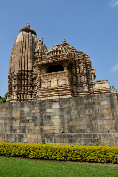 """Khajuraho - Land Of The Moon God is located in the Indian state of Madhya Pradesh (MP) and roughly 620 kilometers (385 miles) southeast of New Delhi. Khajuraho was the cultural capital of the Chandela Rajputs, a Hindu dynasty that ruled from the 10th to 12th centuries. The temples of Khajuraho are famous for their so-called """"erotic sculptures"""".<br /> <br /> Symbolising a medieval legacy, the Khajuraho temples are a perfect fusion of architectural and sculptural excellence, representing one of the finest examples of Indian art. To some, they are the most graphic, erotic and sensuous sculptures the world has ever known. But Khajuraho has not received the attention it deserves for its significant contribution to the religious art of India - there are literally hundreds of exquisite images on the interior and exterior walls of the shrines.<br /> <br /> Architecturally they are unique. While each temple has a distinct plan and design, several features are common to all. They are all built on high platforms, several metres off the ground. The stone used throughout is either granite or a combination of light sandstone and granite. Each of these temples has an entrance hall or mandapa, and a sanctum sanctorum or garbha griha. The roofs of these various sections have a distinct form. The porch and hall have pyramidal roofs made of several horizontal layers. The inner sanctum's roof is a conical tower - a colossal pile of stone (often 30m high) made of an arrangement of miniature towers called shikharas."""