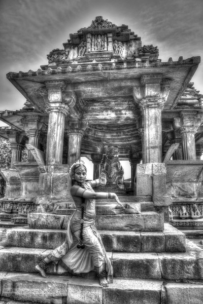 """Kuchipudi dancer Abhinaya Nagajothy at the Khajuraho Temple. <br /> Khajuraho - Land Of The Moon God is located in the Indian state of Madhya Pradesh (MP) and roughly 620 kilometers (385 miles) southeast of New Delhi. Khajuraho was the cultural capital of the Chandela Rajputs, a Hindu dynasty that ruled from the 10th to 12th centuries. The temples of Khajuraho are famous for their so-called """"erotic sculptures"""".<br /> <br /> Symbolising a medieval legacy, the Khajuraho temples are a perfect fusion of architectural and sculptural excellence, representing one of the finest examples of Indian art. To some, they are the most graphic, erotic and sensuous sculptures the world has ever known. But Khajuraho has not received the attention it deserves for its significant contribution to the religious art of India - there are literally hundreds of exquisite images on the interior and exterior walls of the shrines.<br /> <br /> Architecturally they are unique. While each temple has a distinct plan and design, several features are common to all. They are all built on high platforms, several metres off the ground. The stone used throughout is either granite or a combination of light sandstone and granite. Each of these temples has an entrance hall or mandapa, and a sanctum sanctorum or garbha griha. The roofs of these various sections have a distinct form. The porch and hall have pyramidal roofs made of several horizontal layers. The inner sanctum's roof is a conical tower - a colossal pile of stone (often 30m high) made of an arrangement of miniature towers called shikharas."""