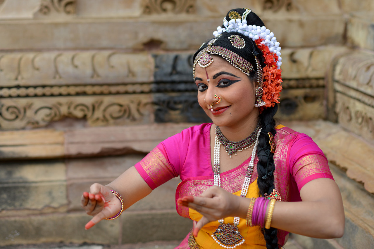 "Kuchipudi dancer Abhinaya Nagajothy displays different mudras at the Khajuraho Temple. <br /> Khajuraho - Land Of The Moon God is located in the Indian state of Madhya Pradesh (MP) and roughly 620 kilometers (385 miles) southeast of New Delhi. Khajuraho was the cultural capital of the Chandela Rajputs, a Hindu dynasty that ruled from the 10th to 12th centuries. The temples of Khajuraho are famous for their so-called ""erotic sculptures"".<br /> <br /> Symbolising a medieval legacy, the Khajuraho temples are a perfect fusion of architectural and sculptural excellence, representing one of the finest examples of Indian art. To some, they are the most graphic, erotic and sensuous sculptures the world has ever known. But Khajuraho has not received the attention it deserves for its significant contribution to the religious art of India - there are literally hundreds of exquisite images on the interior and exterior walls of the shrines.<br /> <br /> Architecturally they are unique. While each temple has a distinct plan and design, several features are common to all. They are all built on high platforms, several metres off the ground. The stone used throughout is either granite or a combination of light sandstone and granite. Each of these temples has an entrance hall or mandapa, and a sanctum sanctorum or garbha griha. The roofs of these various sections have a distinct form. The porch and hall have pyramidal roofs made of several horizontal layers. The inner sanctum's roof is a conical tower - a colossal pile of stone (often 30m high) made of an arrangement of miniature towers called shikharas."