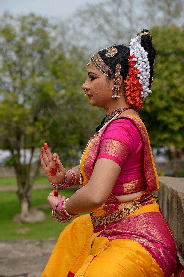 "Kuchipudi dancer Abhinaya Nagajothy in a pose at the Khajuraho Temple. <br /> Khajuraho - Land Of The Moon God is located in the Indian state of Madhya Pradesh (MP) and roughly 620 kilometers (385 miles) southeast of New Delhi. Khajuraho was the cultural capital of the Chandela Rajputs, a Hindu dynasty that ruled from the 10th to 12th centuries. The temples of Khajuraho are famous for their so-called ""erotic sculptures"".<br /> <br /> Symbolising a medieval legacy, the Khajuraho temples are a perfect fusion of architectural and sculptural excellence, representing one of the finest examples of Indian art. To some, they are the most graphic, erotic and sensuous sculptures the world has ever known. But Khajuraho has not received the attention it deserves for its significant contribution to the religious art of India - there are literally hundreds of exquisite images on the interior and exterior walls of the shrines.<br /> <br /> Architecturally they are unique. While each temple has a distinct plan and design, several features are common to all. They are all built on high platforms, several metres off the ground. The stone used throughout is either granite or a combination of light sandstone and granite. Each of these temples has an entrance hall or mandapa, and a sanctum sanctorum or garbha griha. The roofs of these various sections have a distinct form. The porch and hall have pyramidal roofs made of several horizontal layers. The inner sanctum's roof is a conical tower - a colossal pile of stone (often 30m high) made of an arrangement of miniature towers called shikharas."