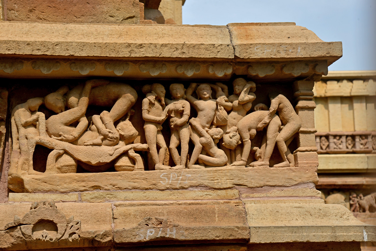 """Stone carvings at Khajuraho. Khajuraho - Land Of The Moon God is located in the Indian state of Madhya Pradesh (MP) and roughly 620 kilometers (385 miles) southeast of New Delhi. Khajuraho was the cultural capital of the Chandela Rajputs, a Hindu dynasty that ruled from the 10th to 12th centuries. The temples of Khajuraho are famous for their so-called """"erotic sculptures"""".<br /> <br /> Symbolising a medieval legacy, the Khajuraho temples are a perfect fusion of architectural and sculptural excellence, representing one of the finest examples of Indian art. To some, they are the most graphic, erotic and sensuous sculptures the world has ever known. But Khajuraho has not received the attention it deserves for its significant contribution to the religious art of India - there are literally hundreds of exquisite images on the interior and exterior walls of the shrines.<br /> <br /> Architecturally they are unique. While each temple has a distinct plan and design, several features are common to all. They are all built on high platforms, several metres off the ground. The stone used throughout is either granite or a combination of light sandstone and granite. Each of these temples has an entrance hall or mandapa, and a sanctum sanctorum or garbha griha. The roofs of these various sections have a distinct form. The porch and hall have pyramidal roofs made of several horizontal layers. The inner sanctum's roof is a conical tower - a colossal pile of stone (often 30m high) made of an arrangement of miniature towers called shikharas."""