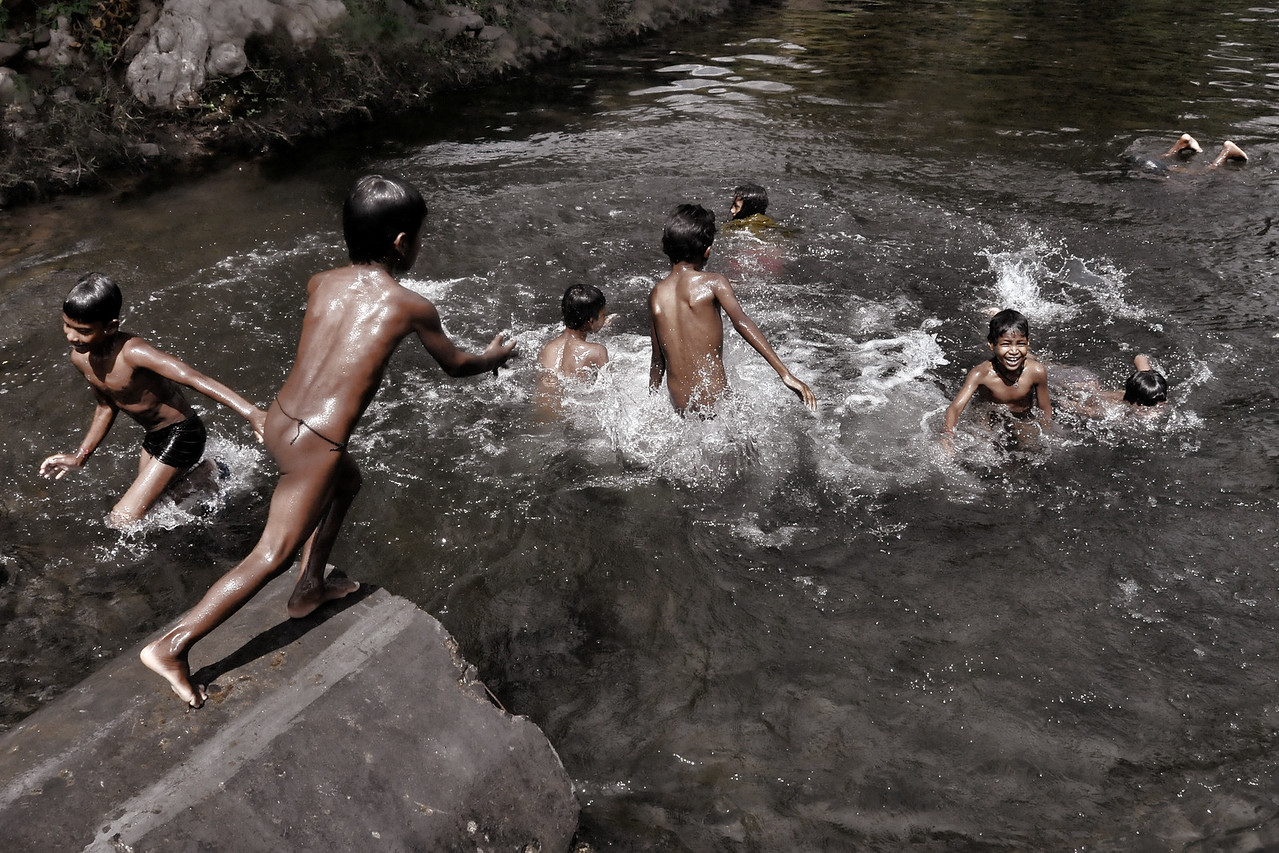 Young children bathing and having fun in an open water body in rural Maharashtra.