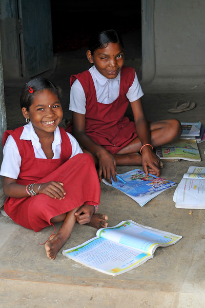 Girls in school uniforms studying and doing home work.<br /> Villages in rural India in the state of Maharashtra.