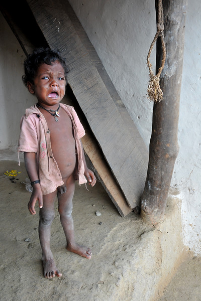 Young boy crying out loudly in his village.<br /> Villages in rural India in the state of Maharashtra.