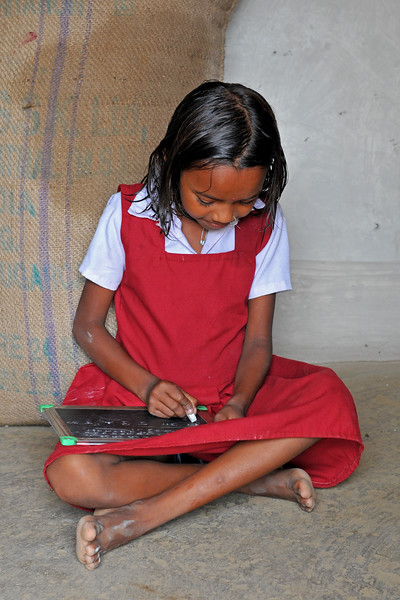 Little girl studying at her village using chalk and slate.<br /> Villages in rural India in the state of Maharashtra.