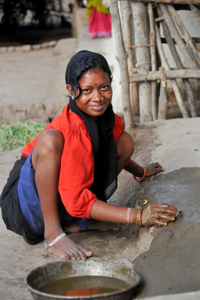 Village girl using dung to make the house flooring. Villages in rural India in the state of Maharashtra.