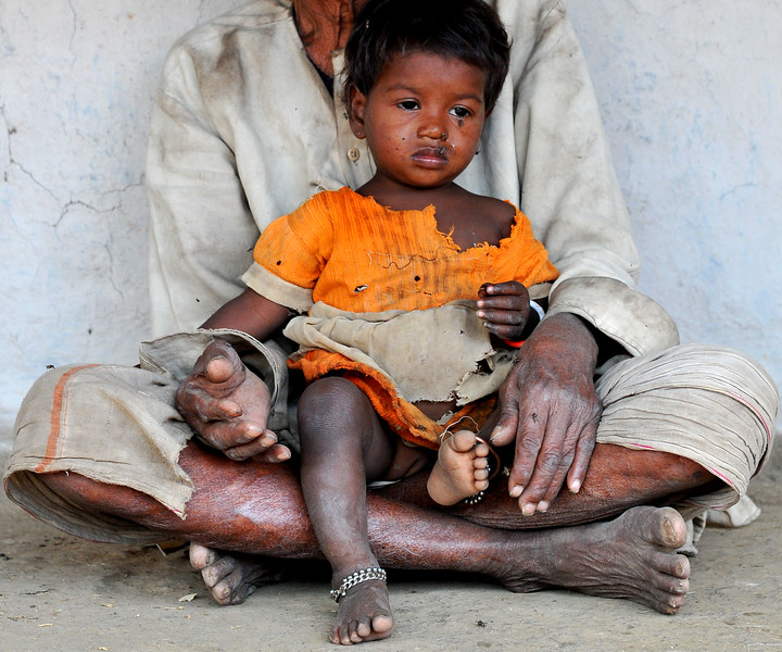 Young girl in her grandfather's lap at their village.<br /> Villages in rural India in the state of Maharashtra.