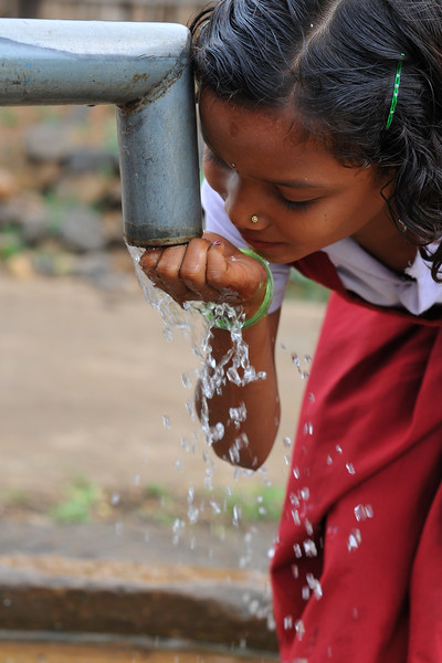 Getting water from the hand pump for drinking.<br /> Villages in rural India in the state of Maharashtra.