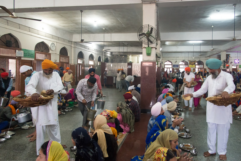 "Everyone sits on the floor and receives the same food as prasad (offering) at no cost without restrictions of quantity at The Harmandir Sahib (Punjabi: ਹਰਿਮੰਦਰ ਸਾਹਿਬ), also Darbar Sahib (Punjabi: ਦਰਬਾਰ ਸਾਹਿਬ, )(The abode of God), and informally called the ""Golden Temple"", is the holiest Sikh gurdwara located in the city of Amritsar, Punjab, North India."