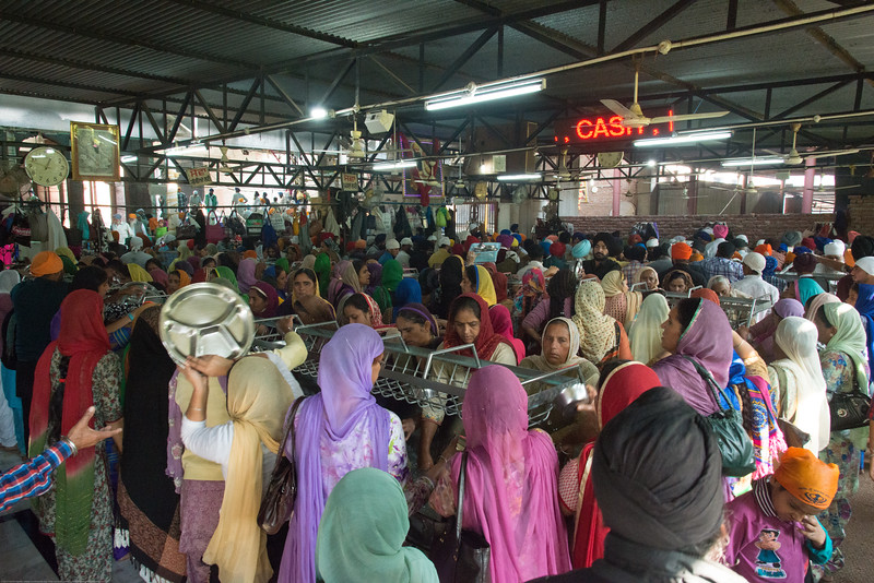 "Women and men do service at the langar where thousands have a meal as prasad.<br /> <br /> The Harmandir Sahib (Punjabi: ਹਰਿਮੰਦਰ ਸਾਹਿਬ), also Darbar Sahib (Punjabi: ਦਰਬਾਰ ਸਾਹਿਬ, )(The abode of God), and informally called the ""Golden Temple"", is the holiest Sikh gurdwara located in the city of Amritsar, Punjab, North India."