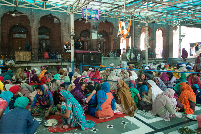 """Women and men do service at the langar where thousands have a meal as prasad.<br /> <br /> The Harmandir Sahib (Punjabi: ਹਰਿਮੰਦਰ ਸਾਹਿਬ), also Darbar Sahib (Punjabi: ਦਰਬਾਰ ਸਾਹਿਬ, )(The abode of God), and informally called the """"Golden Temple"""", is the holiest Sikh gurdwara located in the city of Amritsar, Punjab, North India."""