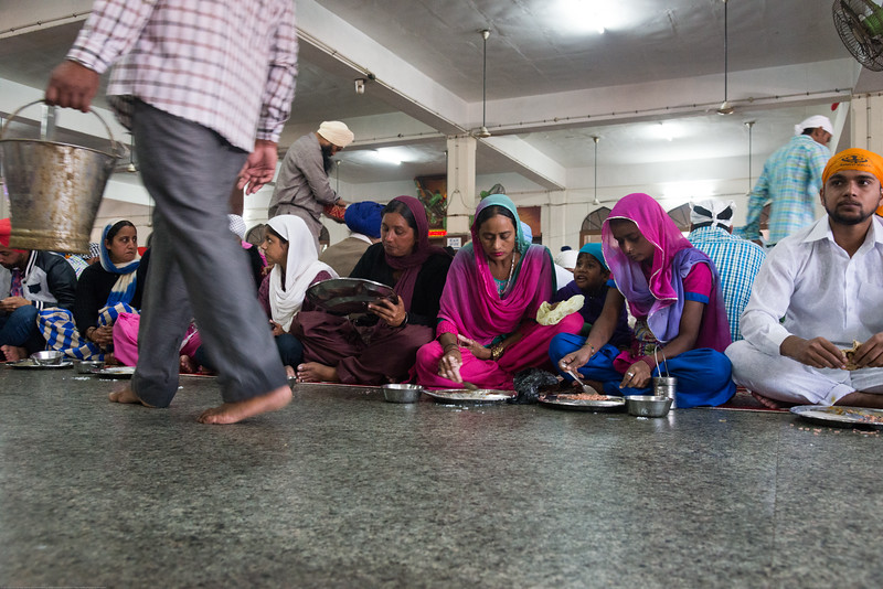 """Everyone sits on the floor and receives the same food as prasad (offering) at no cost without restrictions of quantity at The Harmandir Sahib (Punjabi: ਹਰਿਮੰਦਰ ਸਾਹਿਬ), also Darbar Sahib (Punjabi: ਦਰਬਾਰ ਸਾਹਿਬ, )(The abode of God), and informally called the """"Golden Temple"""", is the holiest Sikh gurdwara located in the city of Amritsar, Punjab, North India."""