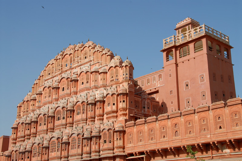 <b><i>The Hawa Mahal</b></i> (Palace of Winds) is one of the Jaipur's major landmarks, although it is actually little more than a facade. Built in 1799, this five-storey building which looks out over the main street of the buzzing old city is a stunning example of Rajput artistry with its pink, delicately honeycombed sandstone windows, of which there are 953. It was originally built to enable the women of the royal household to watch the everyday life and processions of the city. The palace was built by Maharaja Sawai Pratap Singh and is a part of the city palace complex.