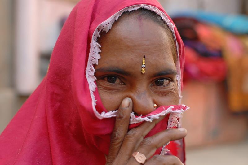 Traditionally saree dressed Rajasthani lady hiding her face as she was shy. Shot near Hawa Mahal, Jaipur, Rajasthan, RJ, India.