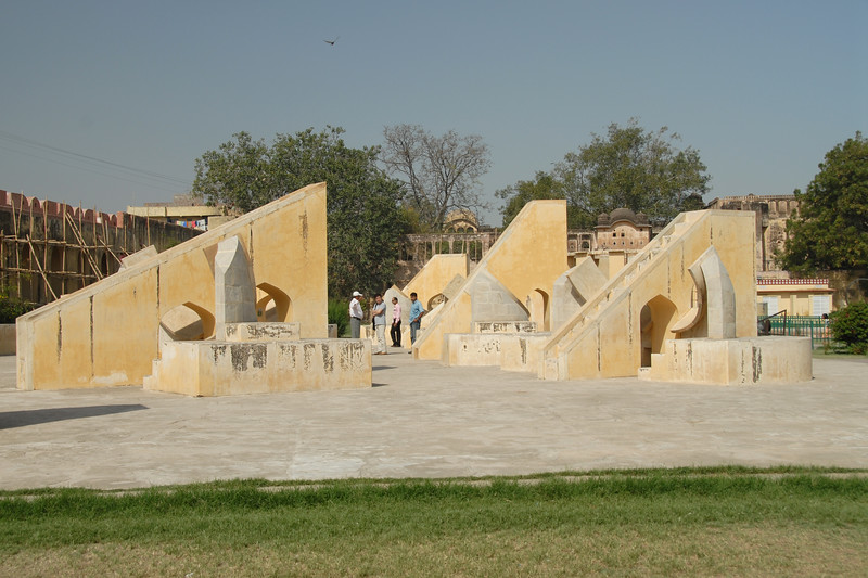 Jantar Mantar, Jaipur, Rajasthan, India<br /> <br /> <br /> In Sanskrit, 'Jantar Mantar' is used for 'Magical Devices' and it is undoubtedly so with the huge masonry instruments, which were placed here to measure 'the harmony of the heavens'. Conceived and constructed by Sawai Raja Jai Singh II, it was completed in seven years (1728 to 1734). Each instrument that forms a part of this observatory is assigned and used for a particular function and is known to give an accurate reading. The Samrat Yantra is a large sundial that looks like a triangular structure and is marked with hours and minutes. The arc at the left shows the time from sunrise to midday while the arc at the right side shows the time from midday to sunset. The time is read by observing where the shadow is sharpest at the time. The sundials have been constructed on latitude 27o north and to adjust the reading to the Indian standard Time (IST), one has to add anything between 1 minute 15 seconds to 32 minutes according to the time of year and solar position. The Dhruva Yantra is used to locate the position of 12 Zodiac signs and also the Pole Star at night. The traditional unit of measurement started with the smallest unit being 'human breath' that has been calculated to be of 6 seconds duration. According to this scale, 4 breaths or 24 seconds equals 1 pal, 60 pals or 24 minutes equals 1 ghadi and 60 ghadis or 24 hours equals 1 day. The Narivalya Yantra is a distinctive sundial with two dials - the first dial facing south reads time when the sun is in the southern hemisphere, i.e., from 21 September to 21 March each year and the other one facing north reads time for the rest of the year when the Sun is in the northern hemisphere, i.e., from 21 March to 21 September. The various other instruments include Jai Singh's seat (the seat of the Observer), Kranti Yantra used for direct measurement of the longitude and latitude of the extraterrestrial bodies, Raj Yantra or the King of Instruments used only once a