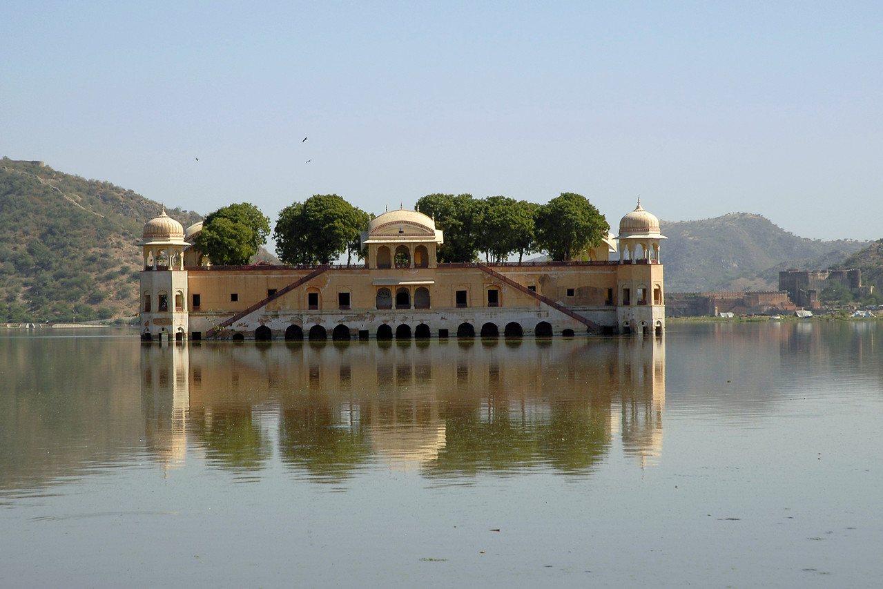 """Jal Mahal (""""Water Palace"""") is an 18th century pleasure palace and is located in Jaipur (Capital of Rajasthan State). The palace is amidst Mansagar lake, which is nestled amongst the Nahargarh hills. The Jal Mahal Palace, Jaipur is noted for its sophisticated design and grand architecture. The first four floors of this building is under water, only the top floor remains outside. This image has been shot enroute the Nahargarh Fort which was built in 1799 and from which one gets a nice view of the Palace, Lake and surrounding areas. The palace itself is now abandoned, but reasonably well preserved."""