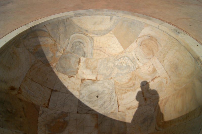 That's me (Suchit Nanda) and my shadow on the Sundial at Jantar Mantar, Jaipur, Rajasthan, India<br /> <br /> <br /> In Sanskrit, 'Jantar Mantar' is used for 'Magical Devices' and it is undoubtedly so with the huge masonry instruments, which were placed here to measure 'the harmony of the heavens'. Conceived and constructed by Sawai Raja Jai Singh II, it was completed in seven years (1728 to 1734). Each instrument that forms a part of this observatory is assigned and used for a particular function and is known to give an accurate reading. The Samrat Yantra is a large sundial that looks like a triangular structure and is marked with hours and minutes. The arc at the left shows the time from sunrise to midday while the arc at the right side shows the time from midday to sunset. The time is read by observing where the shadow is sharpest at the time. The sundials have been constructed on latitude 27o north and to adjust the reading to the Indian standard Time (IST), one has to add anything between 1 minute 15 seconds to 32 minutes according to the time of year and solar position. The Dhruva Yantra is used to locate the position of 12 Zodiac signs and also the Pole Star at night. The traditional unit of measurement started with the smallest unit being 'human breath' that has been calculated to be of 6 seconds duration. According to this scale, 4 breaths or 24 seconds equals 1 pal, 60 pals or 24 minutes equals 1 ghadi and 60 ghadis or 24 hours equals 1 day. The Narivalya Yantra is a distinctive sundial with two dials - the first dial facing south reads time when the sun is in the southern hemisphere, i.e., from 21 September to 21 March each year and the other one facing north reads time for the rest of the year when the Sun is in the northern hemisphere, i.e., from 21 March to 21 September. The various other instruments include Jai Singh's seat (the seat of the Observer), Kranti Yantra used for direct measurement of the longitude and latitude of the extraterrestrial bodies, Raj Yantra or the King of Instruments used only once a year to calculate