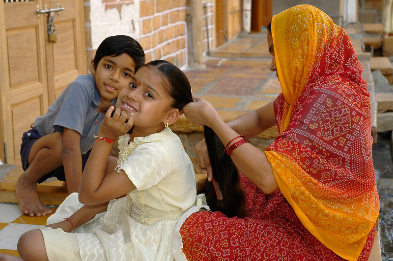 Little girl's grooming taking place outside their home in Jaisalmer City, Rajasthan, India.