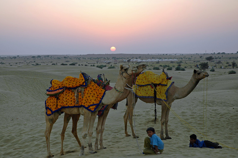 Camel and its keeper in Sam sand dunes of Jaisalmer, Rajasthan, India.