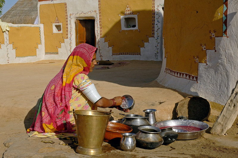 Lady washing vessels in a village home not far from Sam sand dunes of Jaisalmer, Rajasthan, India.