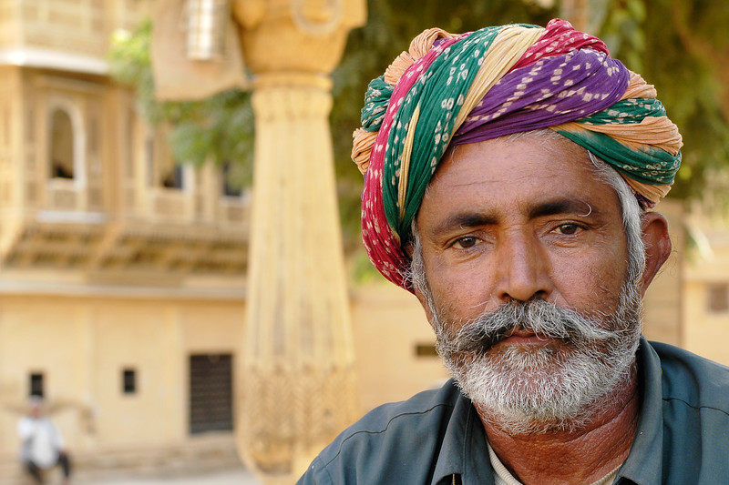 Bright turbaned man sitting outside under the shade. Jaisalmer City, Rajasthan, India.