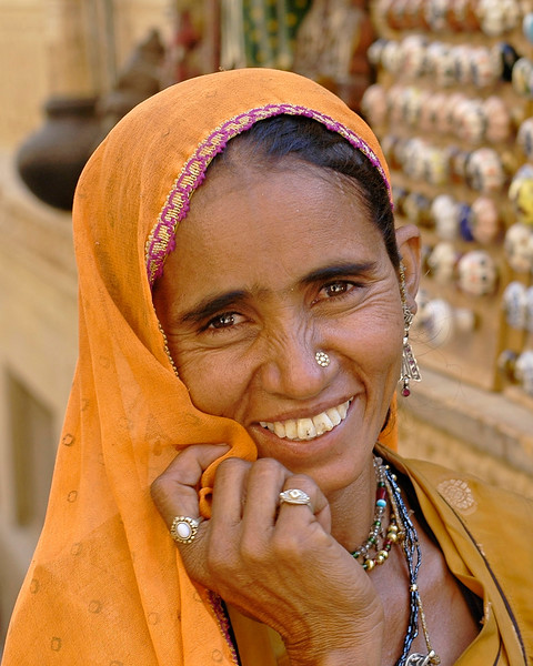 Lady in the Jaisalmer City, Rajasthan, India. South Asia. Seen at the back are ceramic door knobs on sale.