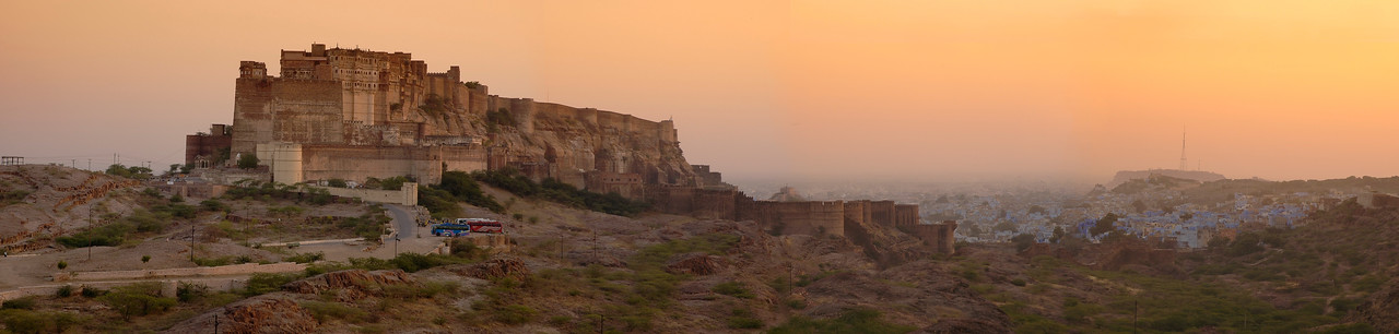 Panoramic image shot of Mehrangarh Fort, Jodhpur in the evening light of the setting Sun. The Mehrangarh Fort is spread over an area of 5 sq. km in the heart of the city. The fort has seven gates  Seen in the foreground are tourist buses that bring lots of visitors daily to the Fort. Jodhpur, Rajasthan, Western India.