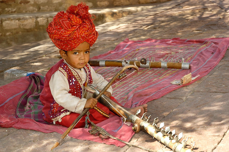 Little boy playing a musical instrument in Mehrangarh Fort, Jodhpur is situated at an altitude of about 125 metres, the Mehrangarh Fort is spread over an area of 5 sq. km in the heart of the city. Jodhpur, Rajasthan, Western India.