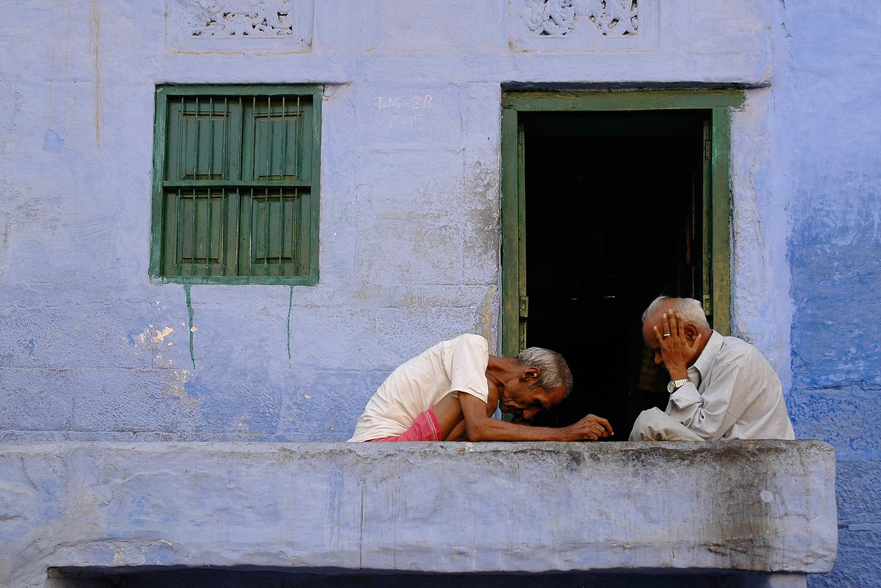 Two elderly men deeply engrossed in their daily life in the blue city of Jodhpur. Jodhpur is a very popular places for tourists to experience life in Rajasthan, India.