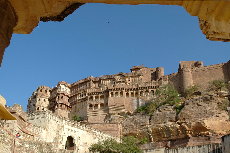 Magnificent Mehrangarh, one of Rajasthan's finest forts, looks down protectively over the city, from the hilltop. The fort is situated at an altitude of about 125 metres and is spread over an area of 5 sq. km with seven gates. One could drive up or walk to the top of the small and not so steep hill. Driving or walking up, the sheer rock face from where emerges the tall and massive sandstone wall of Mehrangarh looks awesome indeed. The fort has seven gates of which the noted ones are the Jayapol, built by Maharaja Man Singh in 1806; Fatehpol or the Victory Gate built by Maharaja Ajit Singh; and the Lohapol or the Iron Gate. The 15 handprints, the sati marks of Maharaja Man Singh's widows who threw themselves upon his funeral pyre in 1843, can be seen beside the Lohapol. On the wall, one can see the strategically located cannons. Jodhpur, Rajasthan, Western India.