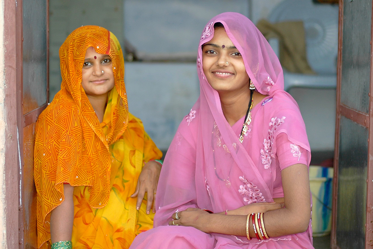Daughter-in-law on the left and daughter on the right sitting at the entrance to their home in Jodhpur city. Jodhpur is a very popular places for tourists to experience life in Rajasthan, India.