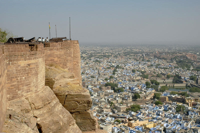 View of the city from inside Mehrangarh Fort, Jodhpur. Inside the fort, a series of courtyards and palaces greet the visitor. The palace apartments house a splendid collection of the trappings of the Indian royalty. The fort is visited by thousands of tourists every year who come to have a glimpse of the artillery system of the Rajput warriors. One can have a bird's eye view of the city from the fort. Situated at an altitude of about 125 metres, the Mehrangarh Fort is spread over an area of 5 sq. km in the heart of the city. The fort has seven gates of which the noted ones are the Jayapol, built by Maharaja Man Singh in 1806; Fatehpol or the Victory Gate built by Maharaja Ajit Singh; and the Lohapol or the Iron Gate. The 15 handprints, the sati marks of Maharaja Man Singh's widows who threw themselves upon his funeral pyre in 1843, can be seen beside the Lohapol. On the wall, one can see the strategically located cannons. Jodhpur, Rajasthan, Western India.