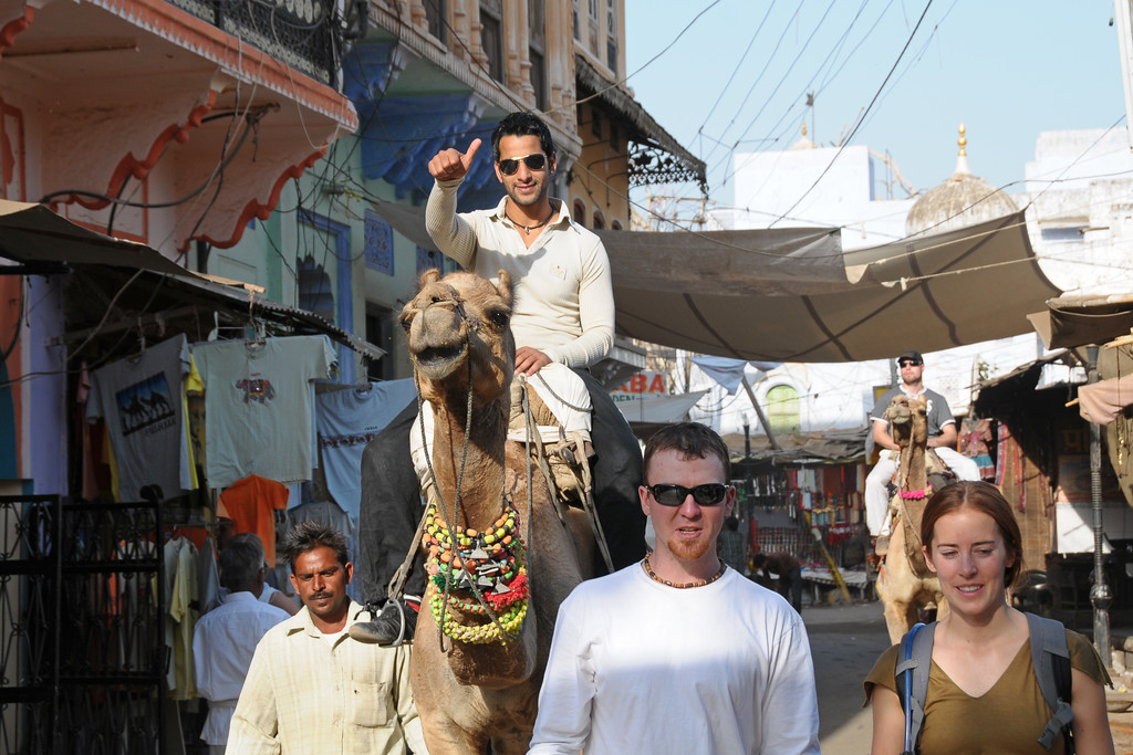 Camel ride in the streets of Pushkar.<br /> <br /> The town of Pushkar is located 14 km North West of Ajmer. Pushkar is one of the oldest cities of India. It  has in recent years become a popular destination for foreign tourists. Pushkar, Rajasthan, India.
