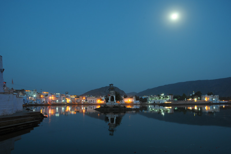 Evening view of Pushkar Lake, Rajasthan with the moon reflecting on the lake.<br /> <br /> The town of Pushkar is located 14 km North West of Ajmer. Pushkar is one of the oldest cities of India. It  has in recent years become a popular destination for foreign tourists. Pushkar, Rajasthan, India.