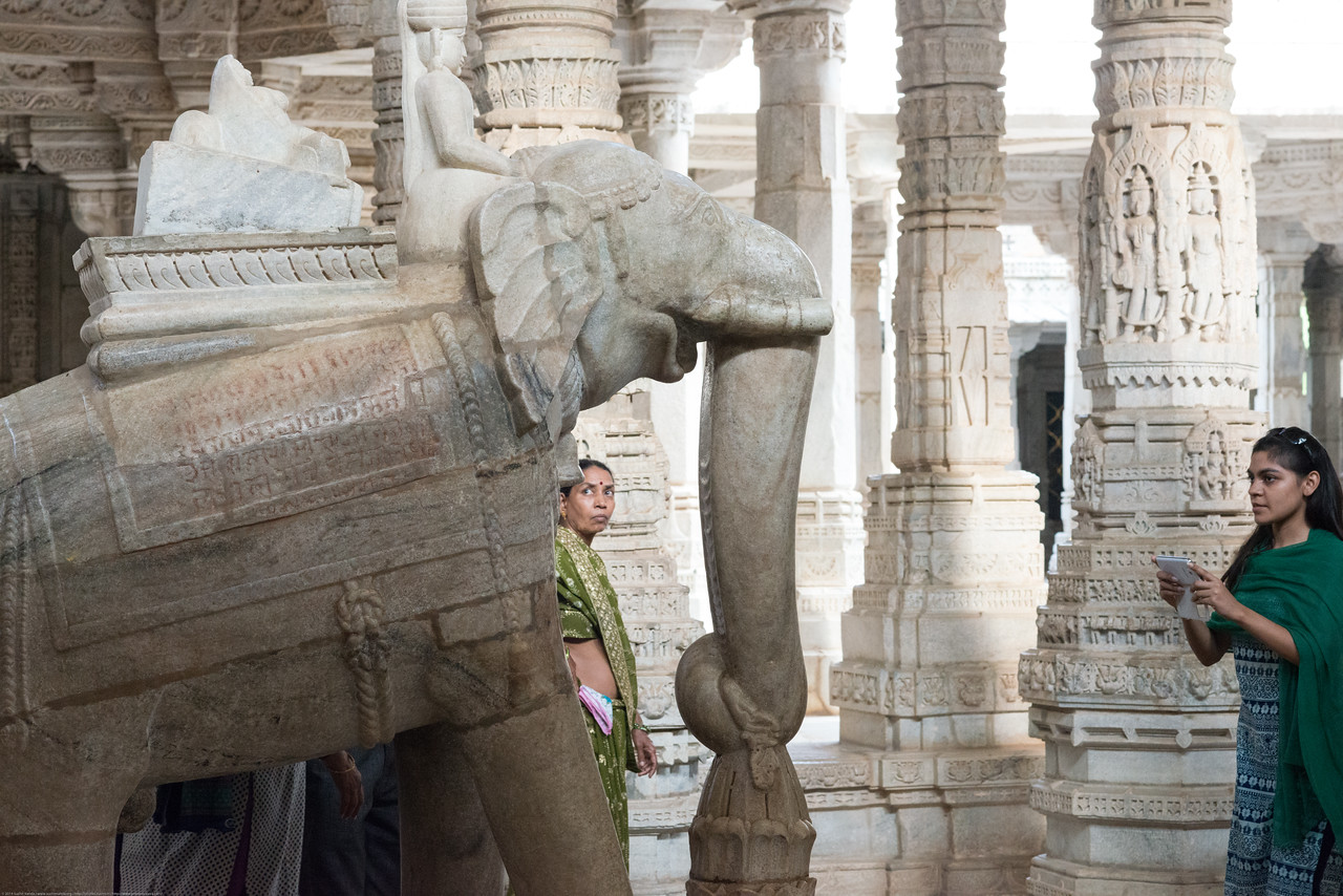 Visitors taking pictures and selfies near the elephant statue inside the large Jain temple in Ranakpur, Rajasthan, India. Ranakpur Jain Temple is dedicated to Tirthankara Adinatha, and said to be the most spectacular of the Jain temples and is one among the most famous places to visit in Pali, Rajasthan. Constructed between 1437 to 1458, copper-plate inscriptions at the temple record that it was inspired by a dream of a celestial vehicle, Dhanna Shah, with the patronage of Rana Kumbha, then ruler of Mewar.