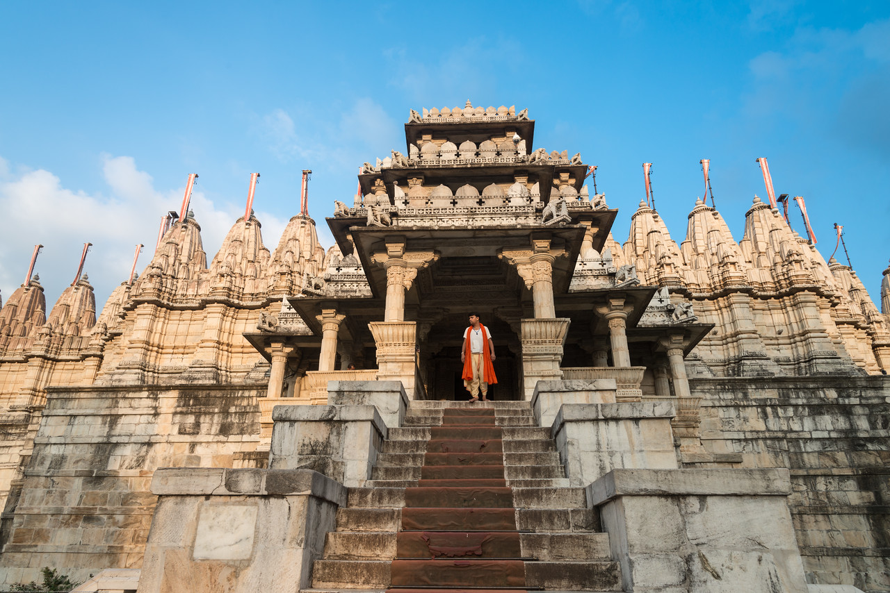 Front Entrance to Ranakpur Jain Temple as a priest walks out.<br /> Ranakpur is widely known for its marble Jain temple dedicated to Tirthankara Adinatha, and said to be the most spectacular of the Jain temples and is one among the most famous places to visit in Pali, Rajasthan. Ranakpur is a village located in a valley on the western side of the Aravalli Range. Near Sadri town in Desuri tehsil in the Pali district of Rajasthan, Western India. It is located between Jodhpur and Udaipur.<br /> <br /> Constructed between 1437 to 1458, copper-plate inscriptions at the temple record that it was inspired by a dream of a celestial vehicle, Dhanna Shah, with the patronage of Rana Kumbha, then ruler of Mewar.