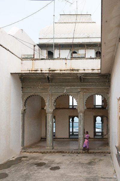 Sweet little girl strikes a pose on her own at The Monsoon Palace (Sajjan Garh Palace). She is the daughter of the caretaker of the hilltop palatial residence, Udaipur, Rajasthan, India.