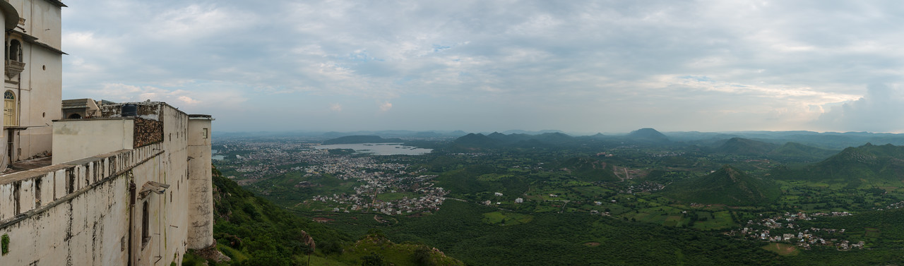 Panoramic view from The Monsoon Palace (Sajjan Garh Palace)  a hilltop palatial residence in the city of Udaipur, Rajasthan in India. The palace, built with white marble, is located on Bansdara peak of the Aravalli hill range at an elevation of 944 m (3100 ft) above mean sea level, overlooking Lake Pichola from the west about 1,100 ft (340 m) below the palace. The intention of the original planner, Maharana Sajjan Singh, was to build a nine storey complex, basically as an astronomical centre and to keep track of the movement of monsoon clouds in the area surrounding the palace, and also to provide employment to people. It was also meant to serve as a resort for the royal family.