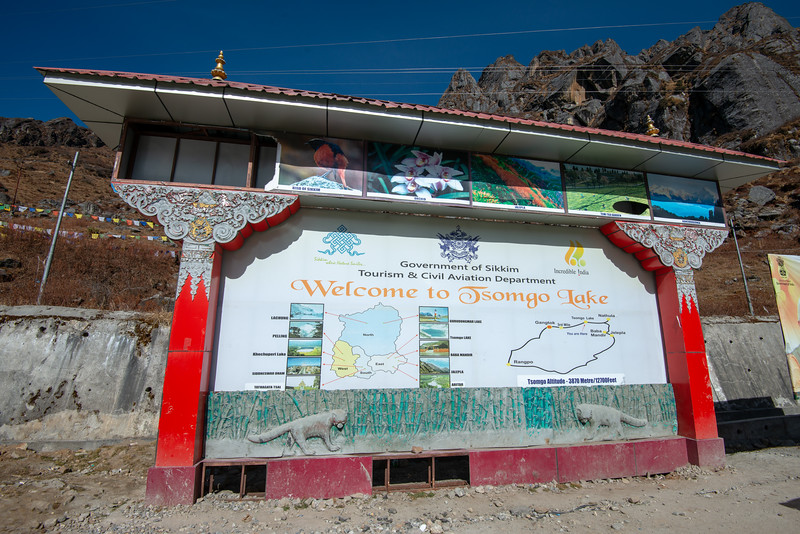 Sign board at Tsomgo Lake (त्सोम्गो लेक) shore offering yak rides during season. The Tsomgo lake at an altitude of over 10,000 ft is surrounded by mountains.