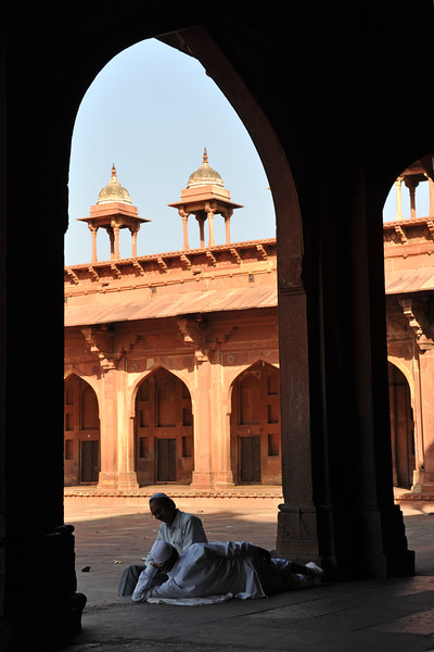 People relax from the heat in the shade.<br /> <br /> Fatehpur Sikri (Hindi: फतेहपुर सीकरी, Urdu: فتحپور سیکری) is a city and a municipal board in Agra district in the state of Uttar Pradesh, in North India. The historical city was constructed by Mughal Emperor Akbar beginning in 1570 and served as the empire's capital from 1571 until 1585. Though it took 15 years to build, it was abandoned after only 14 years of use because of shortage of water supply which was unable to sustain the growing population. The palace and mosque in Fatehpur Sikri are a tourist attraction and it is an UNESCO World Heritage Site which is about 40 km from the Taj Mahal, Agra. Uttar Pradesh state (UP), North India.