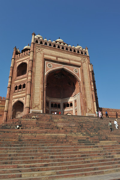 Buland Darwaza: One of the gateways to the Jama Masjid, is a stupendous piece of architecture. Fatehpur Sikri's main entrance is a lofty gate called Buland Darwaza. The Darwaza is 40 metres high and topped by pillars and chhatris. Buland Darwaza is considered to be the greatest architectural monument of Akbar's long reign. The Darwaza was built by Akbar in 1573 to commemorate the conquest of Gujarat.<br />  <br /> Fatehpur Sikri (Hindi: फतेहपुर सीकरी, Urdu: فتحپور سیکری) is a city and a municipal board in Agra district in the state of Uttar Pradesh, in North India. The historical city was constructed by Mughal Emperor Akbar beginning in 1570 and served as the empire's capital from 1571 until 1585. Though it took 15 years to build, it was abandoned after only 14 years of use because of shortage of water supply which was unable to sustain the growing population. The palace and mosque in Fatehpur Sikri are a tourist attraction and it is an UNESCO World Heritage Site which is about 40 km from the Taj Mahal, Agra. Uttar Pradesh state (UP), North India.