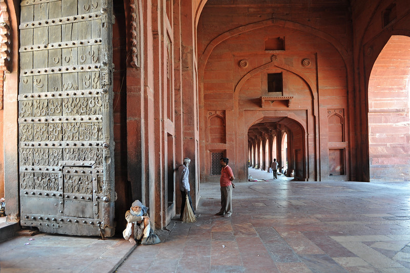 Old man sitting at the entrance asking for some money in the form of donation.<br /> Fatehpur Sikri (Hindi: फतेहपुर सीकरी, Urdu: فتحپور سیکری) is a city and a municipal board in Agra district in the state of Uttar Pradesh, in North India. The historical city was constructed by Mughal Emperor Akbar beginning in 1570 and served as the empire's capital from 1571 until 1585. Though it took 15 years to build, it was abandoned after only 14 years of use because of shortage of water supply which was unable to sustain the growing population. The palace and mosque in Fatehpur Sikri are a tourist attraction and it is an UNESCO World Heritage Site which is about 40 km from the Taj Mahal, Agra. Uttar Pradesh state (UP), North India.
