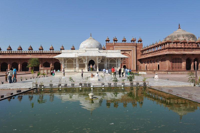 A white marble encased tomb with pond in front within the Jama Masjid's courtyard is the Tomb of Salim Chisti - the sufi saint who lived as a recluse in the small town Sikri near Agra.<br /> <br /> Fatehpur Sikri (Hindi: फतेहपुर सीकरी, Urdu: فتحپور سیکری) is a city and a municipal board in Agra district in the state of Uttar Pradesh, in North India. The historical city was constructed by Mughal Emperor Akbar beginning in 1570 and served as the empire's capital from 1571 until 1585. Though it took 15 years to build, it was abandoned after only 14 years of use because of shortage of water supply which was unable to sustain the growing population. The palace and mosque in Fatehpur Sikri are a tourist attraction and it is an UNESCO World Heritage Site which is about 40 km from the Taj Mahal, Agra. Uttar Pradesh state (UP), North India.