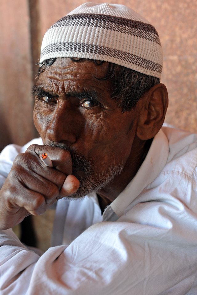 One of the workers at Fatehpur Sikri taking a smoking break.<br /> Fatehpur Sikri (Hindi: फतेहपुर सीकरी, Urdu: فتحپور سیکری) is a city and a municipal board in Agra district in the state of Uttar Pradesh, in North India. The historical city was constructed by Mughal Emperor Akbar beginning in 1570 and served as the empire's capital from 1571 until 1585. Though it took 15 years to build, it was abandoned after only 14 years of use because of shortage of water supply which was unable to sustain the growing population. The palace and mosque in Fatehpur Sikri are a tourist attraction and it is an UNESCO World Heritage Site which is about 40 km from the Taj Mahal, Agra. Uttar Pradesh state (UP), North India.
