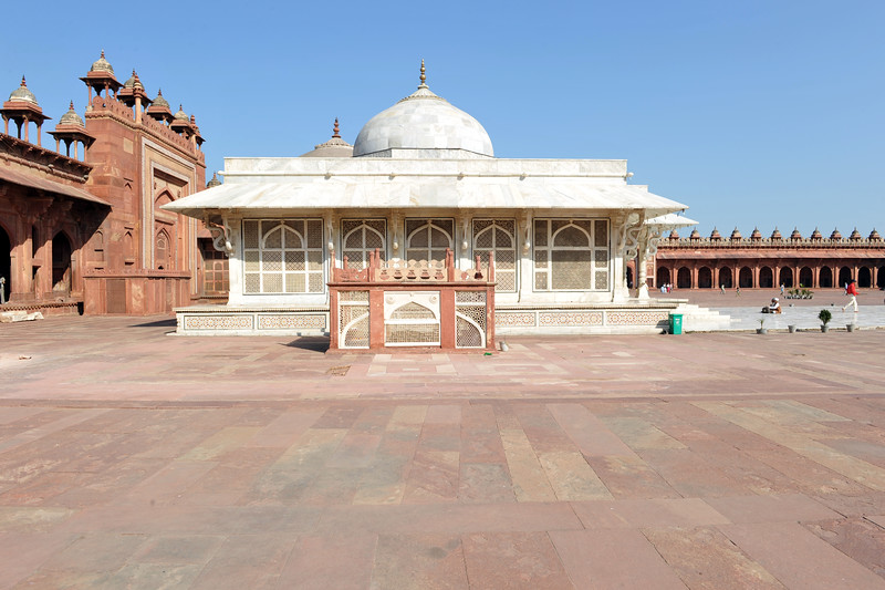 A white marble encased tomb within the Jama Masjid's courtyard is the Tomb of Salim Chisti - the sufi saint who lived as a recluse in the small town Sikri near Agra.<br /> <br /> Fatehpur Sikri (Hindi: फतेहपुर सीकरी, Urdu: فتحپور سیکری) is a city and a municipal board in Agra district in the state of Uttar Pradesh, in North India. The historical city was constructed by Mughal Emperor Akbar beginning in 1570 and served as the empire's capital from 1571 until 1585. Though it took 15 years to build, it was abandoned after only 14 years of use because of shortage of water supply which was unable to sustain the growing population. The palace and mosque in Fatehpur Sikri are a tourist attraction and it is an UNESCO World Heritage Site which is about 40 km from the Taj Mahal, Agra. Uttar Pradesh state (UP), North India.