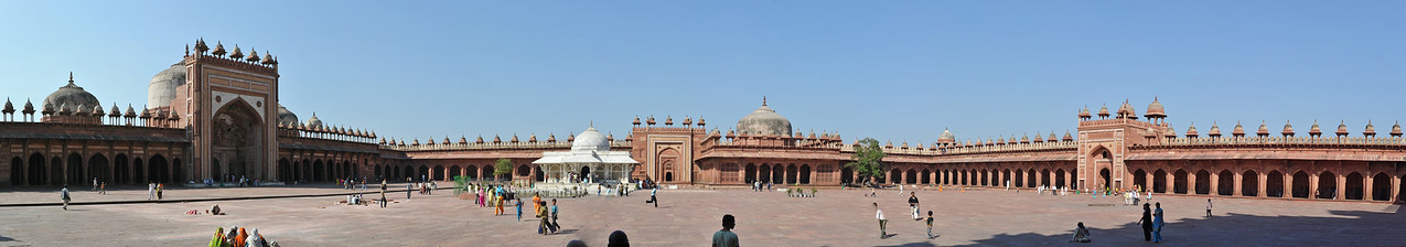 Panoramic view of the tomb of Salim Chisti at Jama Masjid.<br /> A white marble encased tomb within the Jama Masjid's courtyard is the Tomb of Salim Chisti - the sufi saint who lived as a recluse in the small town Sikri near Agra.<br /> <br /> Fatehpur Sikri (Hindi: फतेहपुर सीकरी, Urdu: فتحپور سیکری) is a city and a municipal board in Agra district in the state of Uttar Pradesh, in North India. The historical city was constructed by Mughal Emperor Akbar beginning in 1570 and served as the empire's capital from 1571 until 1585. Though it took 15 years to build, it was abandoned after only 14 years of use because of shortage of water supply which was unable to sustain the growing population. The palace and mosque in Fatehpur Sikri are a tourist attraction and it is an UNESCO World Heritage Site which is about 40 km from the Taj Mahal, Agra. Uttar Pradesh state (UP), North India.